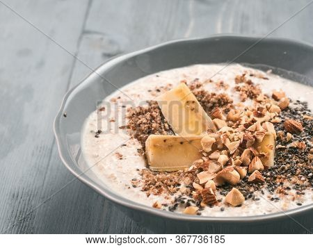 Close Up View Of Overnight Oats In Bowl With Banana, Lsa, Chia Seeds, Almond And Honey On Gray Woode