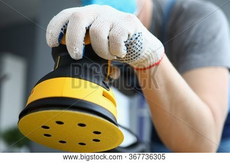 Male Builder In Work Gloves Holds Sander Machine. Preliminary Cleaning And Polishing Surfaces. Carpe