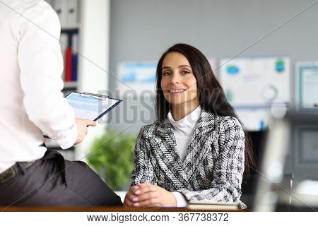 Woman Sitting In Office Front Her Man With Report. Head Perceives Information By Ear, Easily Switch