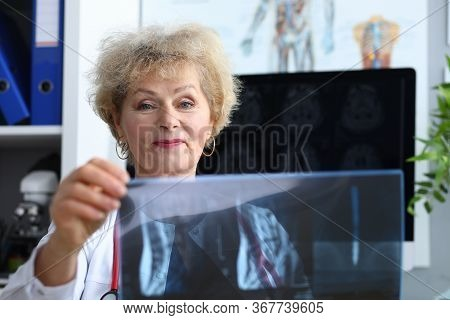 Experienced Doctor Woman Looking At X-ray Office. An Experienced Woman Doctor Is Consulting. Medical
