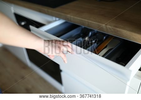 Female Hand Opens Kitchen Drawer With Cutlery. Household Utensils Are In Kitchen Drawer. Spoons And
