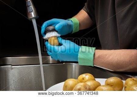 Washing And Rinsing Potatoes With A Vegetable Brush In Preparation For Cooking. Model Wearing Blue R