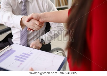 Businessman In Wheelchair Shakes Hands With Woman. Girl Holds Report With Chart In Her Hands. Wheelc