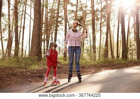 Picture Of Tender Sincere Mother Standing On Road With Her Daughter, Chilling Out Together, Rollerbl