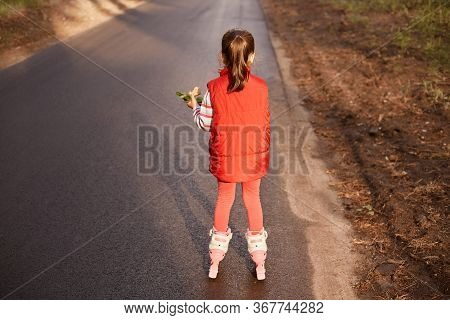 Back View Of Tiny Little Girl With Ponytail Wearing Red Casual Clothes, Holding Food In One Hand, Be