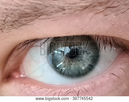 Close Up Young Mans Eye, Look From Under Eyelids. Eye Movements And Gaze Direction. True Intentions