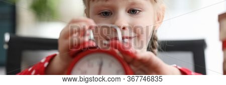 Little Girl Looks With Interest At Red Alarm Clock. Child European Appearance, Carefully Examines Al