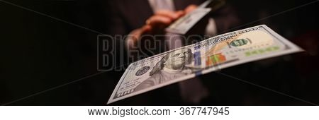 Man In Business Suit Litter Money, Dollars Closeup. Person Spends Thoughtlessly Money On Gambling An