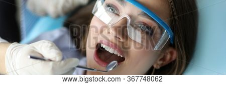 Girl Feels Comfortable At Dental Examination. Routine Check-up Includes Complete Dental Cleaning By