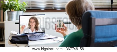 telemedicine concept elderly woman speaking to her doctor online and taking her blood pressure