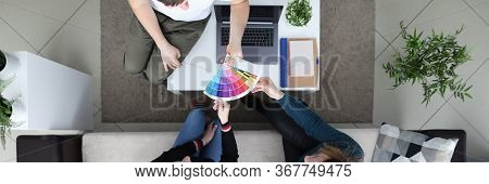 Girl Are Sitting On Couch, Man Shows Color Palette. Girls Choose Color For Painting Walls In Room. G