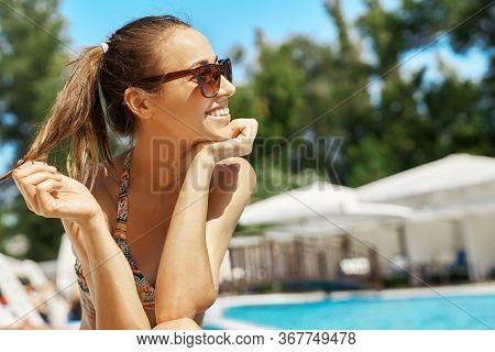 Close Up Portrait Of Beautiful Smiling Girl In Sunglasses Lying At Pool Edge Sunbathing.