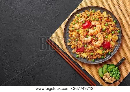Thai Pineapple Fried Rice Or Kao Pad Sapparod On A Black Plate On Dark Slate Backdrop. Kao Pad Sappa