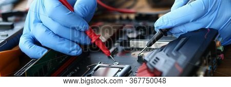 Hands Are Repairing An Electronic Device, Soldering. Service Center For Computer Repair. Restoration