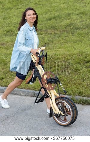 A Beautiful Young Woman Folds Up And Unfolds A Bicycle. Convenient Folding Bike For Travel And Trans