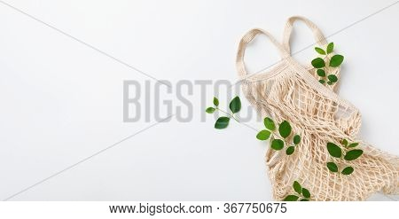 Organic And Reusable Cotton Eco Bag With Green Leaves Top View. Zero Waste And Eco Friendly Concept