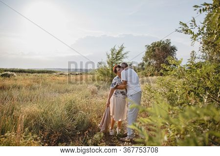 An Old Married Couple On A Summer Walk In The Field. The Couple Hug