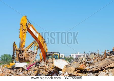 Destruction Of Old Building. Yellow Excavator On Ruins. Photo Smartphone. Smartphone In Hand. Digger
