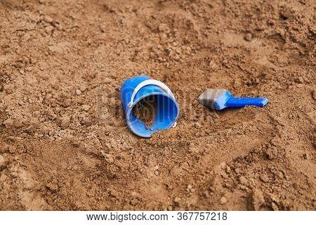 Blue Plastic Children's Bucket And Scoop Are Forgotten In The Sandbox