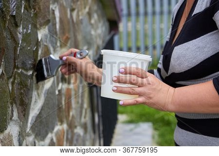 Varnishing Of A Stone, Woman With A Brush Varnishes A Stone At Home