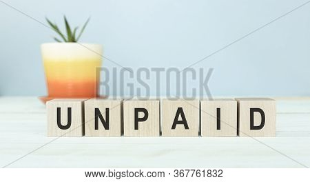 Unpaid Word Written On Wood Block. Unpaid Text On Wooden Table For Your Desing, Concept.