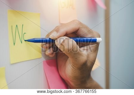 Work. Businessman Hand Writing With Colored Sheets Sticky Note Paper On White Board Background In Ho