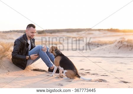 Young Caucasian Man Dressed Black Leather Jacket And Blue Jeans Sits On Sandy Beach Next To His Frie