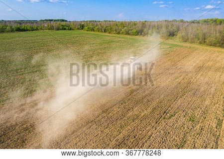 Farmer Cultivates A Field On A Crawler Tractor And Loosens The Soil With A Disc Cultivator Against T