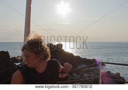 A Caucasic Blond Woman Watching A Sailboat On The Horizon During Sunset At The Beach Bar. Hi Res Pho