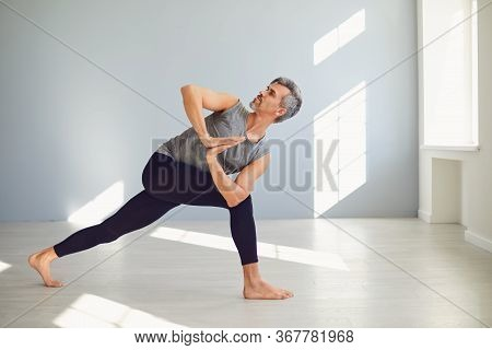 Yoga Man. A Man Is Practicing Yoga Balance In A Gray Room.