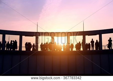 People on the observation deck of skyscraper, Osaka, Japan. Silhouettes of mans and womens on sunset sky background