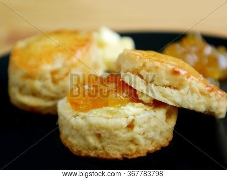 Closeup Of Mouthwatering Candied Orange Zest Scones  With Marmalade Jam On A Black Plate