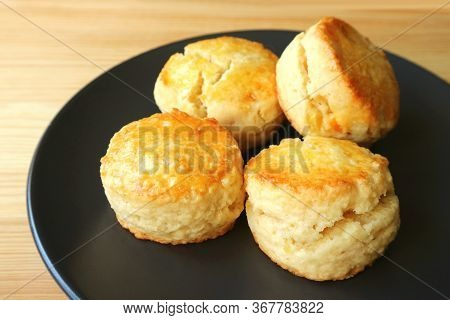 Plate Of Delectable Homemade Candied Orange Zest Scones On Wooden Table