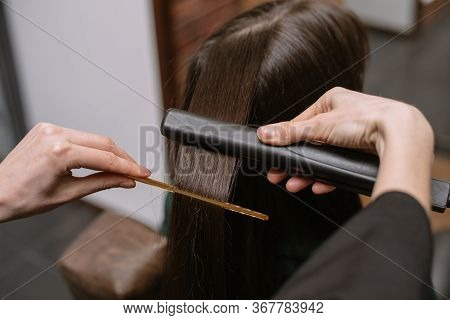 The Hairdresser Pulls And Straightens The Hair Of A Brunette In A Beauty Salon With A Comb And Ironi