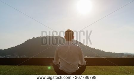 Man Silhouette In White Shirt Meditates In Lotus Pose On Grass On Sunny Day Against Big Green Hill U