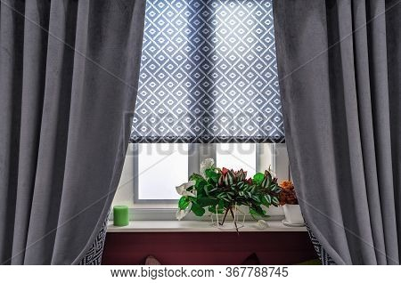Gray Curtains And Fabric Blinds With Ornaments On The Windows In The Living Room.