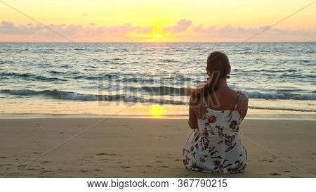 Young Woman In Stylish Summer Dress Sits On Beach Sand Watching Pictorial Ocean At Sunset Time Backs