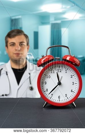 Vintage Red Alarm Clock On Dark Slate Plate With Caucasian Man Posing As A Medical Doctor In A Hospi