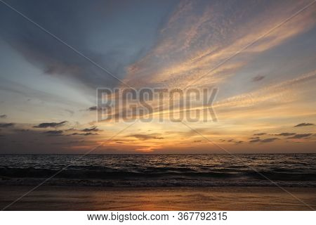 Beautiful View Of Endless Ocean With Wide Rolling Waves Against Pictorial Orange Sky With Clouds At