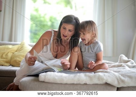 mother and daughter reads a book on sofa at home