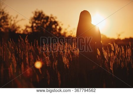 Young Woman Girl In Field In Sunset In Spring, Summer Landscape Background Springtime Summertime. Be