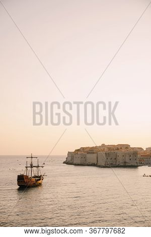 The Old City Of Dubrovnik Against The Sunset Sky. The Wooden Sailing Ship Galleon Approaches The Mai