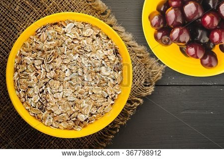 Muesli On A Dark Grah Wooden Table. Muesli On A Yellow Plate Whith Fruits Top View . Healthy Food