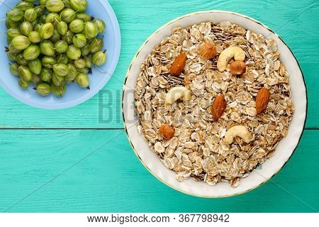 Oatmeal With Nuts On A White Plate With Fruits. Oatmeal On Aturquoise Wooden Table. Oatmeal Top View