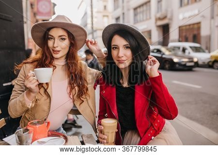 Stunning Brunette Girl In Gray Fedora Spending Time With Ginger Female Friend In Cafe. Two Young Lad