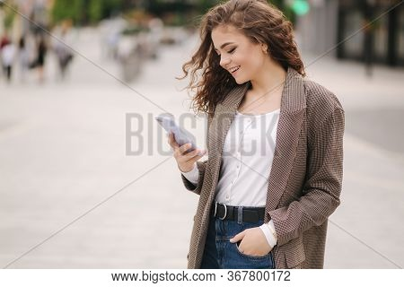 Attractive Young Woman Use Phone In City. Happy Beautiful Woman Writing Massage On Phone, Online
