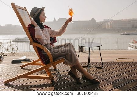 Graceful Young Woman In Hat Sitting On Chaise-longue On River Background. Outdoor Photo Of Caucasian