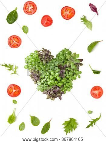 Creative layout made of tomato slices and lettuce salad leaves. Varieties of basil arrangement in form of heart. Flat lay, top view. Food concept. Vegetables isolated on white background.