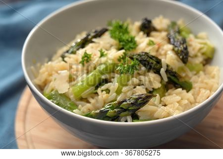 Freshly Cooked Risotto With Green Asparagus, Parmesan And Parsley Garnish In A White Bowl On A Board
