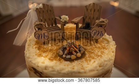 Side View Of A Rustic Style Wedding Cake Themed Around Camping. Close Up Of Adirondack Chairs Cake T
